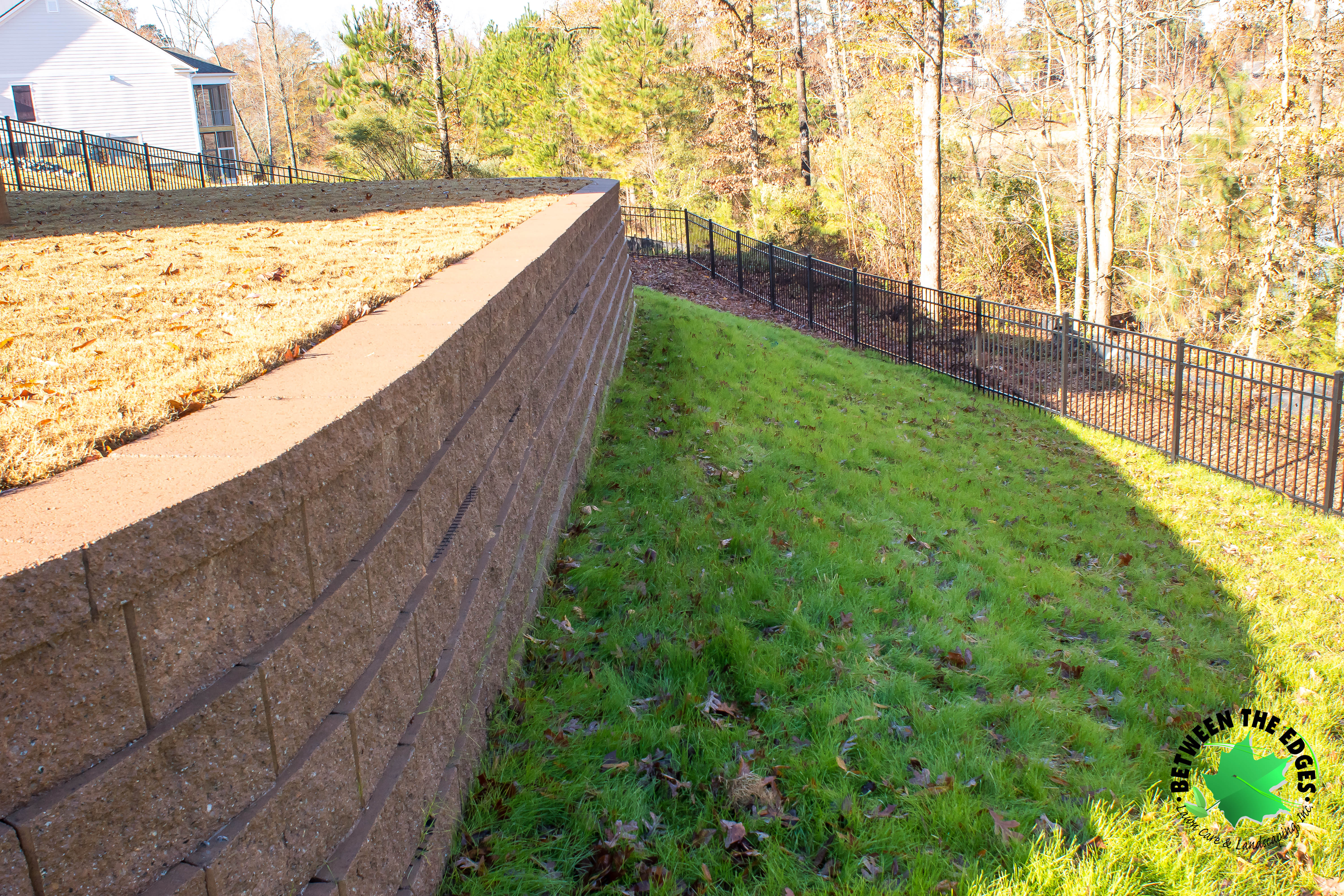 A Retaining Wall And Fence Improve This